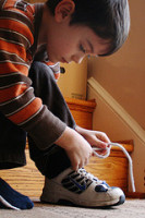 Child tying shoe for the first time
