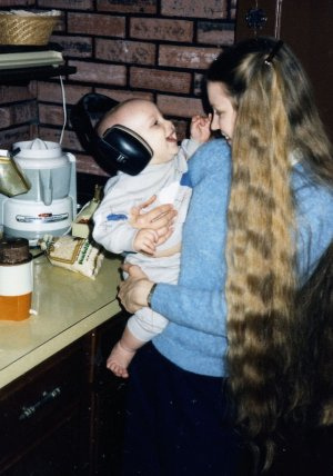 "Will (7 mos.) wearing noise protectors and ""helping"" make organic baby cereal in 1985."