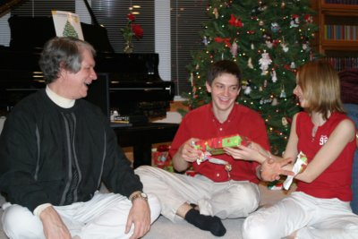 Terry, Will (18), and Christina (13) still enjoying our Christmas Eve traditions in 2003.  Here, Will and Christina are giving each other gifts.