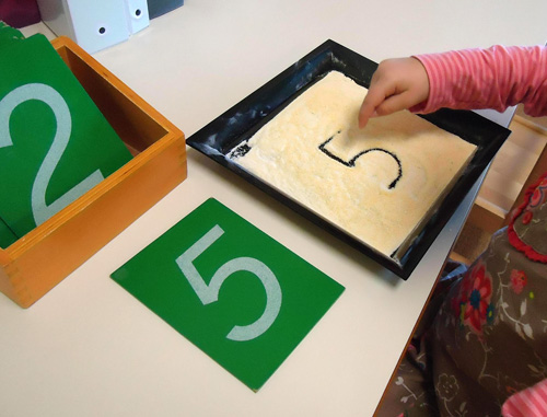Sandpaper Numerals and Cornmeal Writing Tray (Photo from Dirigo Montessori School)