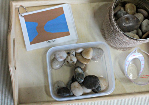 DIY Land and Water Form Tray with Rocks, Water, and Book (Photo from Our Montessori Home)