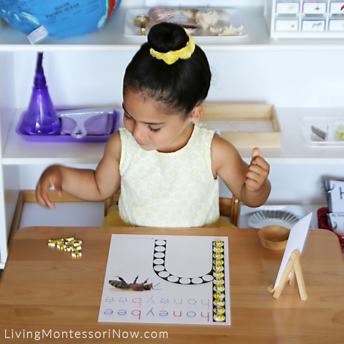 Carefully Lining up Bee Erasers on Honeybee Do-a-Dot Printable