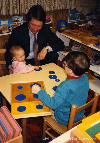 Christina (9 months), Terry, and Will (5). Montessori education encourages kindness and older children helping younger children. Here Will decided to introduce his baby sister to one of the Montessori geometric trays.