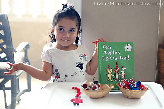 Putting 10 Apples up on Top of Her Photograph