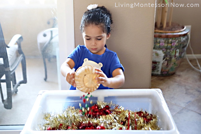 Pouring Bells into Holiday Bell Sensory Bin