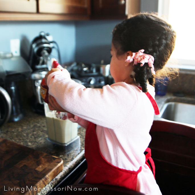 Adding Frozen Strawberries to the Smoothie