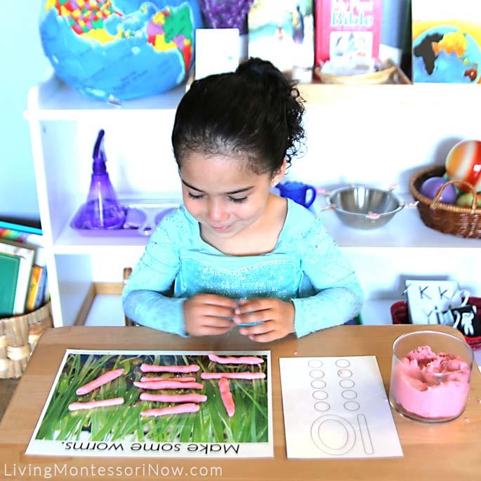 Admiring Her Worm Playdough Math Work