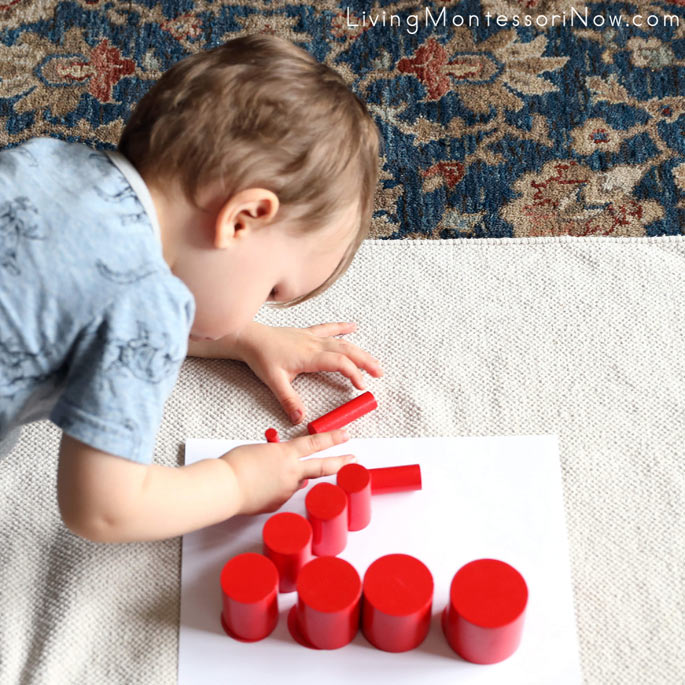 Concentrating on Standing up the Red Knobless Cylinders on a Knobless Cylinder Pattern Card