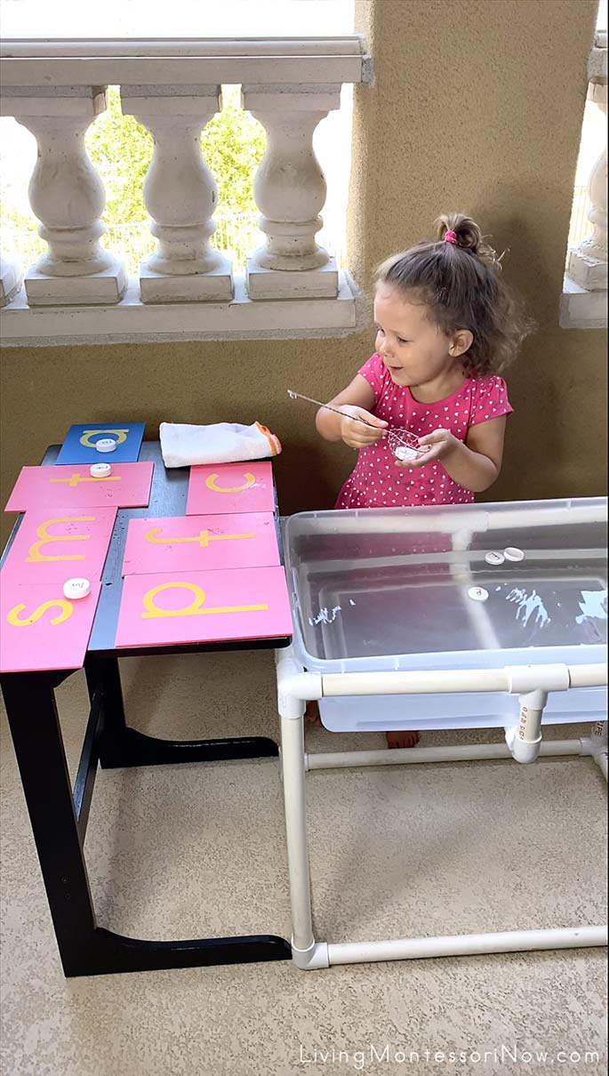 Having Fun Scooping Bottle Cap Letters from Water Table
